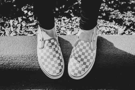 grayscale photography of person wearing checkered slip on shoes